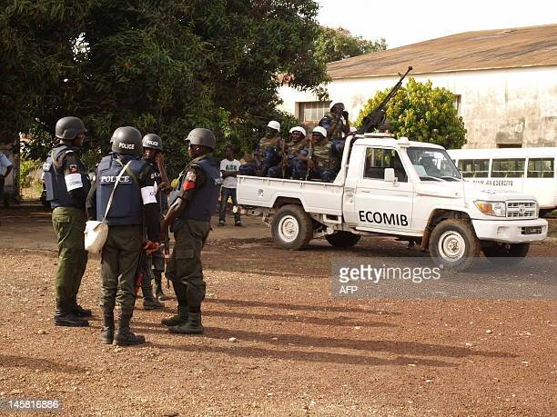 Soldiers and police officers with the Economic Community of West African States mission ECOMIB stand guard at the Bissau airport as Angolan soldiers...