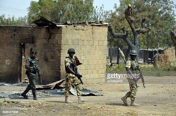 Soldiers and policemen walk past burnt house on February 4 2016 during a visit to the village of Dalori village some 12 kilometres from Borno state...