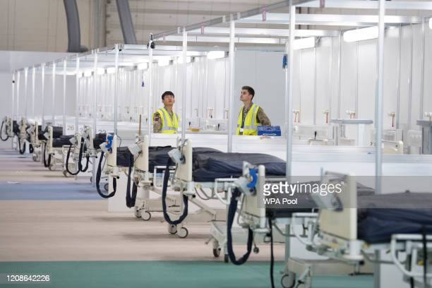 Soldiers and private contractors help to prepare the ExCel centre which is being made into the temporary NHS Nightingale hospital comprising of two...
