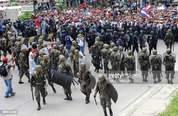 Soldiers and riot squad officers stand guard as supporters of ousted Honduran President Manuel Zelaya participate in a protest against the military...