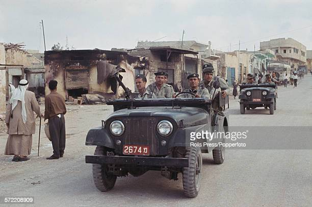 Soldiers and troops of the Israel Defense Forces in a small convoy of Willys jeeps drive past as citizens of the Jordanian West Bank town of Qalqilya...