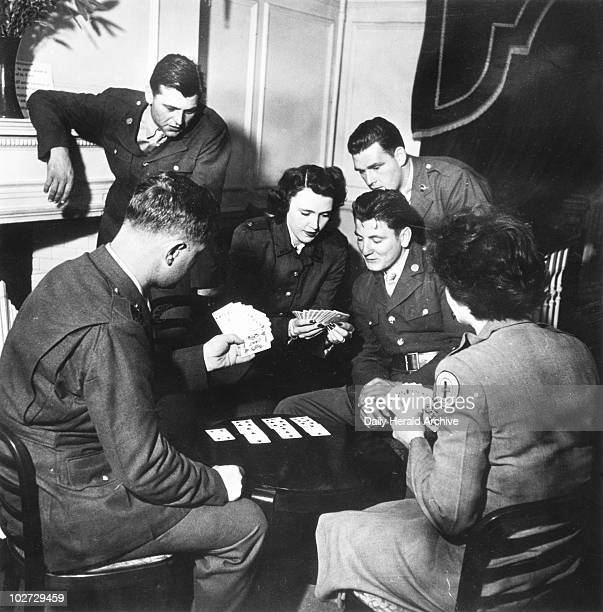 Soldiers and welfare girls playing cards World War Two 1942 'Adelaide consults her partner about a difficult hand Making up a bridge four is part of...