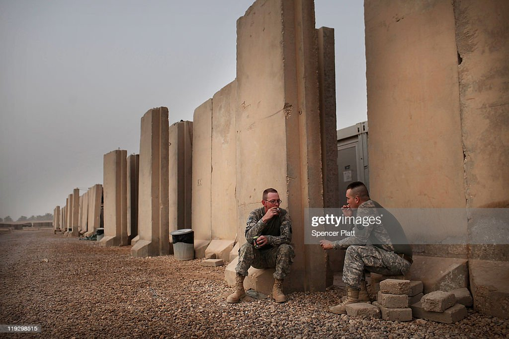 Soldiers Anthony Kittle (R) and William Cameron both of Great Falls, Montana take a cigarette break along a blast wall at base Kalsu on July 17, 2011 in Iskandariya, Babil Province, Iraq. As the deadline for the departure of the remaining American forces in Iraq approaches, Iraqi politicians have been increasingly pressured to meet in order to give a final decision about extending the U.S. troops' presence beyond the end of the 2011 deadline. Violence against foreign troops has recently picked-up with June being the worst month in combat-related deaths for the military in Iraq in more than two years. Currently about 46,000 U.S. soldiers remain in Iraq.