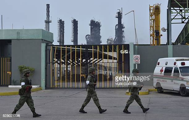 Soldiers are seen as smog covers the staterun oil giant Pemex's Pajaritos petrochemical plant in Coatzacoalcos Veracruz State Mexico a day after an...