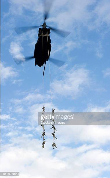 U.S. Soldiers are suspended by a CH-47 Chinook helicopter.