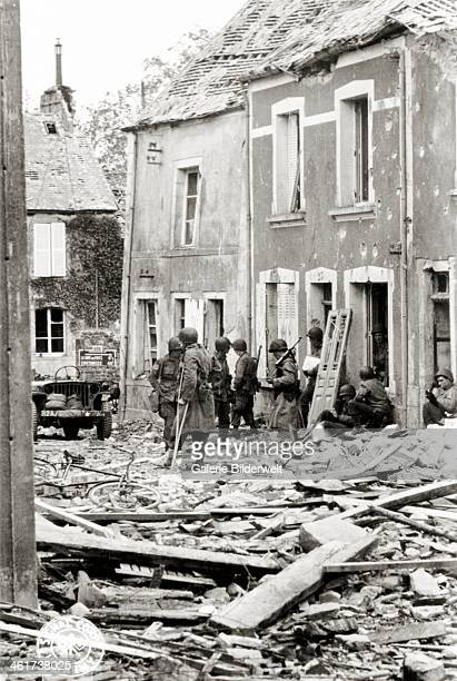 Soldiers are waiting in a street filled with rubble .16th June 1944. These are 2/505th PIR paratroopers of the U.S. 82nd Airborne with their...