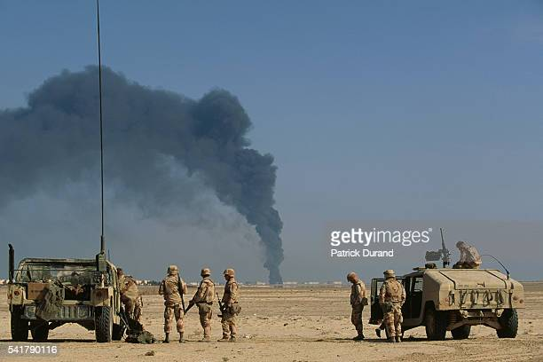 US soldiers arrive at a burning oil refinery in AlKhafji Saudi Arabia near the Kuwait border after Iraqi bombardment during the Gulf War | Location...