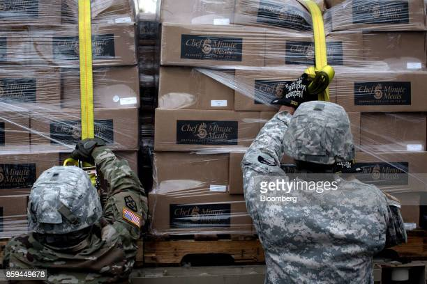 Soldiers assigned to the 1st Mission Support Command US Army Reserve prepare to move boxes of disaster relief meals in Adjuntas Puerto Rico on Friday...