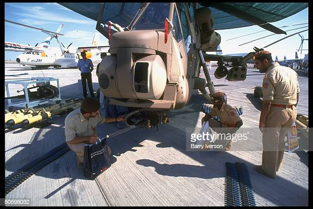 soldiers at S Africanmade Atlas co CSH2 Rooivalk combat copter exhibit at Dubai Air Show featuring civilian mil aircraft arms