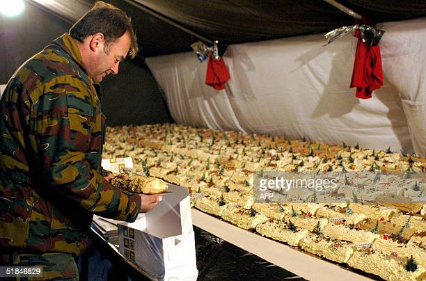 Soldiers based in Tournai sell servings of a 106meterlong Yule Log in support of the victims of the Ghislenghien gas blast 10 December 2004 in Tournai