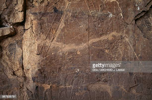 Soldiers besieging a city using the steps relief on an alabaster panel from a palace in Nineveh site was partially destroyed in 2015 Iraq Assyrian...