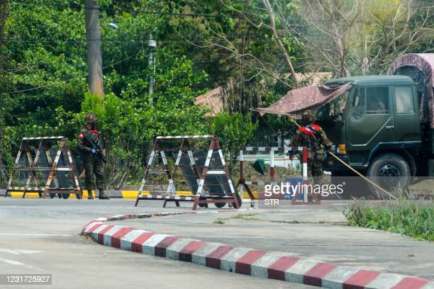 Soldiers block a road near the Parliament building in Naypyidaw on March 14 as demonstrations by protesters against the military coup continue across...