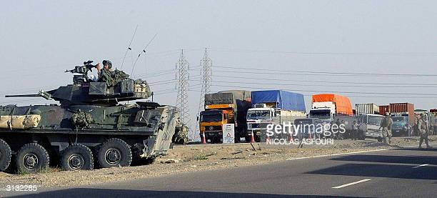 US soldiers block the highway which links Baghdad with the flashpoint town of Ramadi just outside Fallujah 50 kms west of the Iraqi capital 26 March...