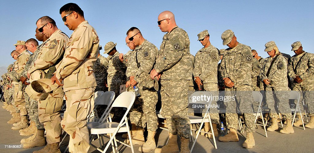 US soldiers bow their heads in prayer during a ceremony at