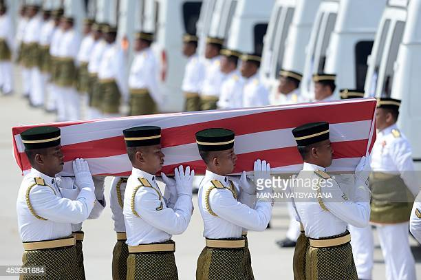 Soldiers carry a coffin with the remains of a Malaysian victim from the Malaysia Airlines flight MH17 that crashed in Ukraine during a ceremony at...