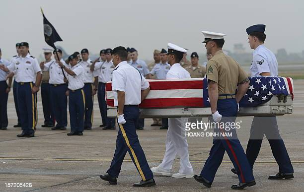 US soldiers carry a US flag draped casket containing what is believed to be remains of a US service man listed as missing in action during the...