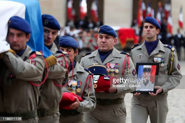 Soldiers carry away the coffins of the 13 French soldiers killed in Mali during a tribute ceremony on December 2, 2019 at the Invalides monument, in...