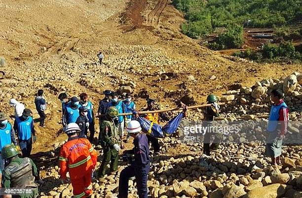 Soldiers carry the bodies of miners killed by a landslide in a jade mining area in Hpakhant in Myanmar's Kachin state on November 22 2015 At least 90...
