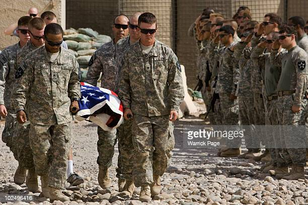 Soldiers carry the body of a US soldier killed in a car bomb attack during a memorial ceremony on June 11, 2010 on FOB Cobra, near Jalula, Diyala...