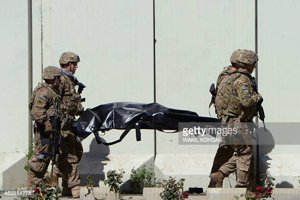 US soldiers carry the body of a victim of a suicide attack in the Afghan capital Kabul on September 16 2014 A Taliban suicide bomber rammed an...