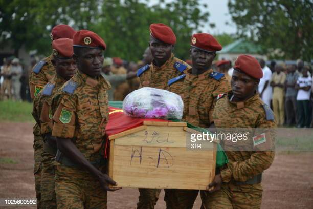 Soldiers carry the coffin of one of the victims during the funeral ceremony of the seven members of the security forces killed three days ago after...