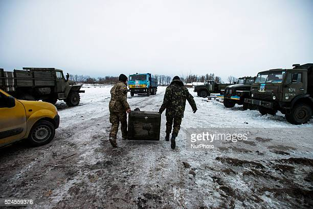 Soldiers carrying fuel tank repaired by volunteers of Victory Sisters Foundation at proving ground near ATO zone Donetsk region Ukraine on January 10...