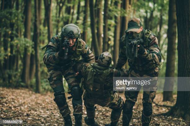 soldiers carrying injured man - battlefield stock pictures, royalty-free photos & images