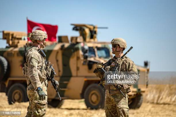 US soldiers chat next to a Turkish military vehicle during a joint patrol with Turkey in the Syrian village of alHashisha on the outskirts of Tal...