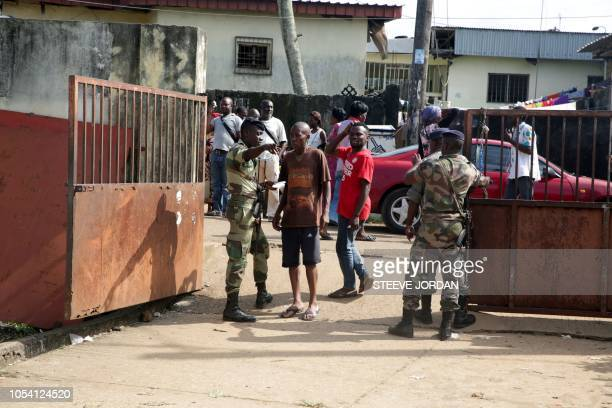 Soldiers check as voters arrive to cast their votes at a polling station in Libreville on October 27 in the second round of legislative elections...