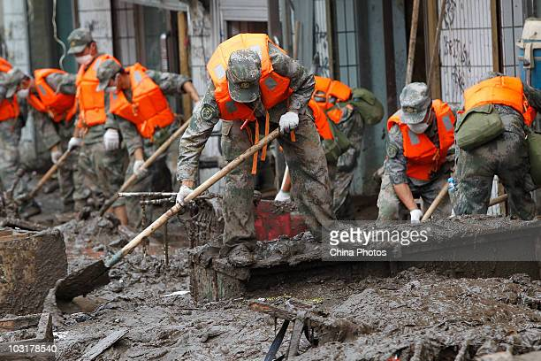 Soldiers clear silt at a floodstricken street after floods swept through the town on July 31 2010 in Kouqian Township Yongji County of Jilin City...