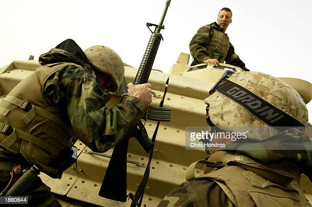 S soldiers climb aboard a tank March 21 2003 in the demilitarized zone along the border of Iraq and Kuwait Troops fought to establish control of the...
