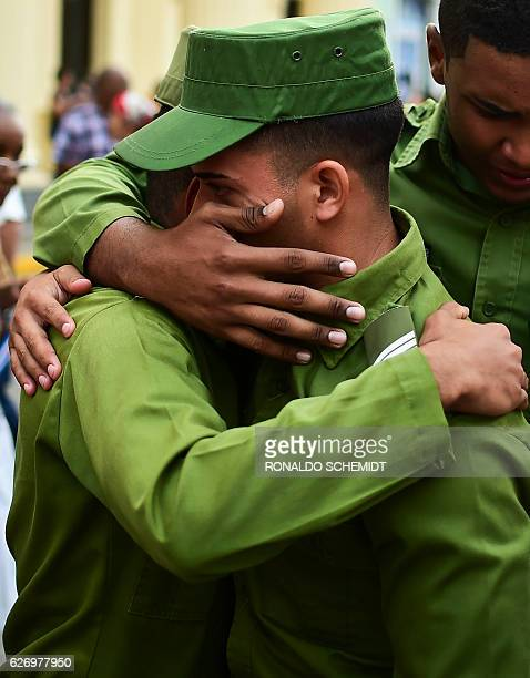 Soldiers comfort each other after the urn with the ashes of Cuban leader Fidel Castro was driven through Santa Clara on December 1 2016 during its...