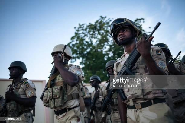 Soldiers conduct the daily flaglowering ceremony at the Force Multinationale Mixte base in Mora in Cameroon's Far North Region on September 28 2018...