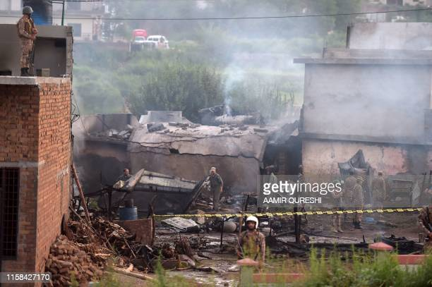 Soldiers cordon off the site where a Pakistani Army Aviation Corps aircraft crashed in Rawalpindi on July 30 2019 Seventeen people were killed when a...