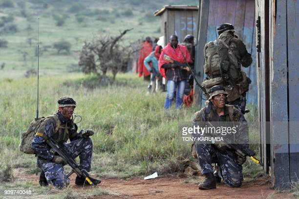 Soldiers defend position at a mock insurgent training camp during a simulated military excercise of the British Army Training Unit in Kenya together...