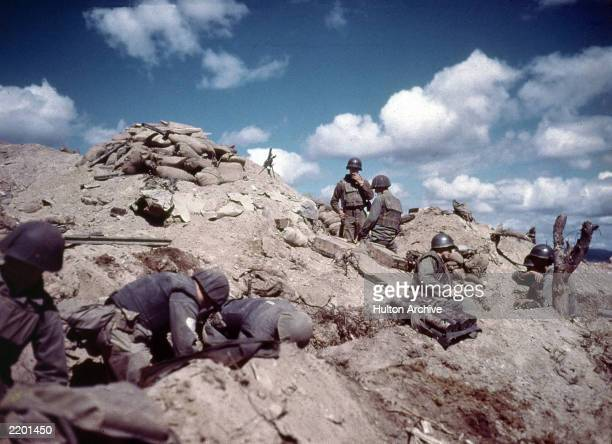 Soldiers dig in to a hill in Korea during the Korean war .