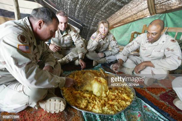 US soldiers dig into a dish of rice and chicken at the house of Sheikh Ali alGhazzi head of the alGhazzi tribe in Nasiriyah 30 November 2003 Sheikh...