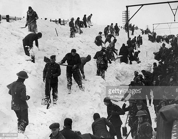 Soldiers dig out a snowbound train on the railway line between Manchester and Sheffield 7th February 1940