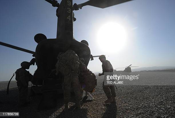 US soldiers disembark from a Chinook helicopter at Forward Operating Base Sharano in Sharano district Paktika province on July 1 2011 The process of...