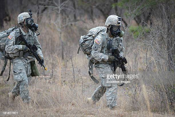 U.S. soldiers don chemical warfare gear.