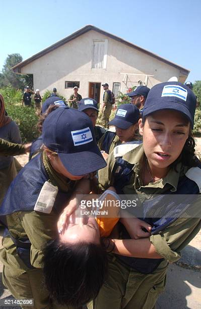 IDF soldiers drag a resistant Jewish settler out of her home in the Jewish settlement of Neve Dekalim part of the Gush Katif settlement bloc Gaza...