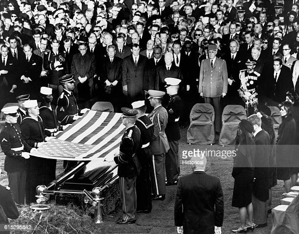 Soldiers drape a flag over the casket of President John F Kennedy in front of a crowd of mourners at Arlington National Cemetery The President's...