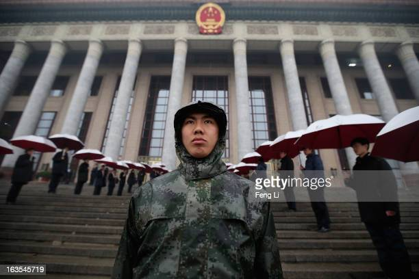 Soldiers dressed as ushers hold umbrellas in the rain at the entrance of the Great Hall of the People as they wait for delegates arrive to the...