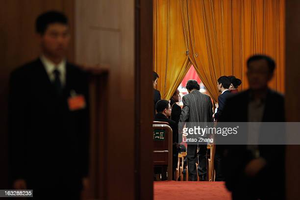 Soldiers dressed as ushers perform guard duties during the a plenary session of the Chinese People's Political Consultative Conference on March 7...