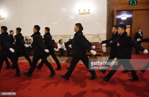Soldiers dressed in suits march before the sixth plenary session of the National People's Congress in the Great Hall of the People in Beijing on...