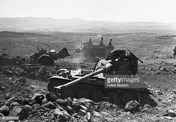 Soldiers drive past a deserted Syrian tank which was captured by the Israelis during the SixDay War