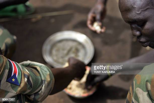 Soldiers eat lunch during a break at Nabanga, south Sudan, on April 12, 2008. The signing of a peace agreement by rebel leader Joseph Kony has been...