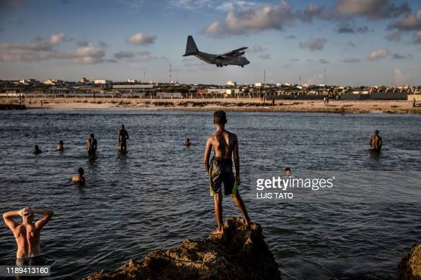 TOPSHOT Soldiers enjoying a day off and Somali people look from the beach at a military plane landing within Mogadishus airport base in Mogadishu...