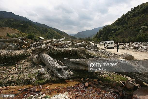 Soldiers escort a car beside logs rushed down from mountains by flood at a village on March 18 2006 in Panwa Kachin State Special Region 1 of Kachin...
