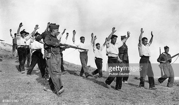 Soldiers escort a contingent of republican fighters who have surrendered their position on the Somosierra Front during the Spanish Civil War .